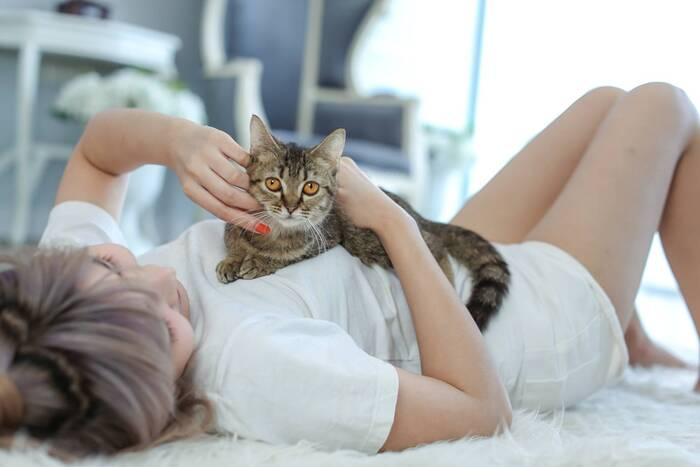woman dressed in white lying on a white carpet on the floor playing with a cat on her chest