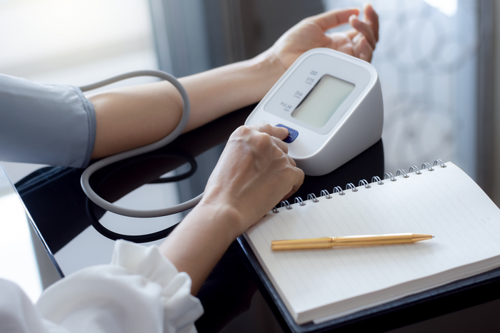 woman measuring blood pressure with on a dark table with a notebook and a pen next to her