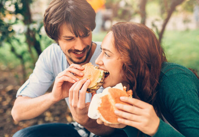 metabolic changes during the year couple eating sandwich together smiling and looking at each other