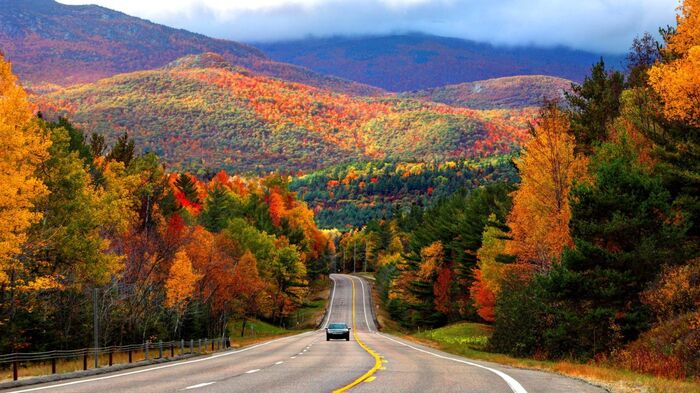 new york area drive in fall mountain landscape and a road with a car on it surrounded by colorful trees