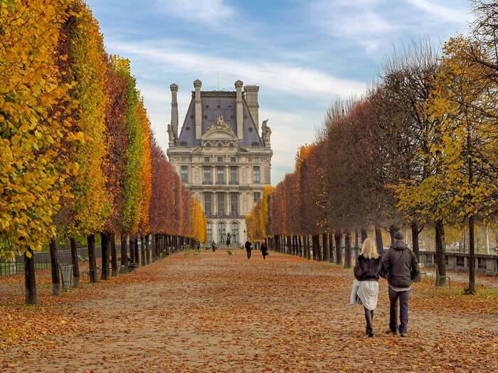 couple walking in Paris in fall colorful tress along an alley and a castle in the background