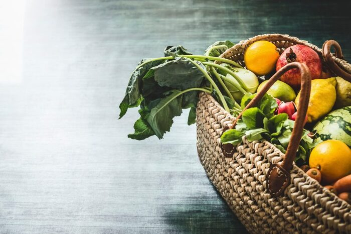 seasonal veggies in a woven basket on the floor pomegranates lemons raddish and other furits and veggies