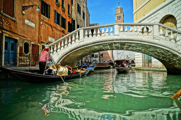a channel in Venice with a bridge and a gondola passing by