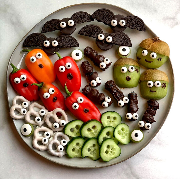 Halloween dish with a variety of halloween veggie snacks ghosts kiwis red peppers cucumber slices and oreo bats