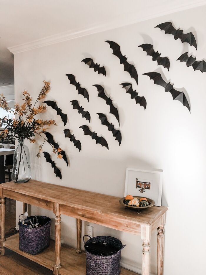 paper bats on a white wall halloween decor in a living space with wooden furniture