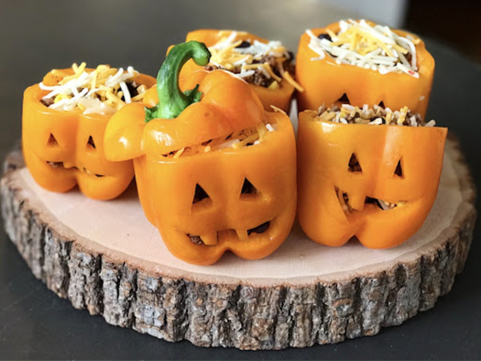 stuffed yellow halloween bell peppers on a wooden piece with carved faces and grated cheese on top