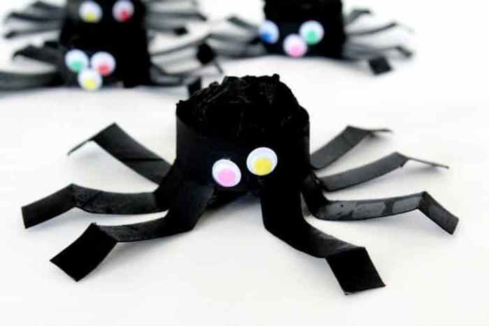 bouncy black spiders on a white table top with colorful eyes