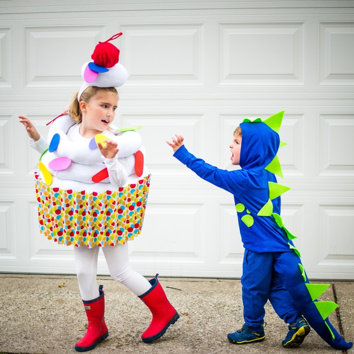 two kids in front of a white garage door dressed in halloween costumes cupcake and blue dragon chasing each other