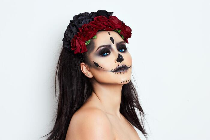 woman with black hair posing on a white background with halloween make up on and a crown of red and black roses