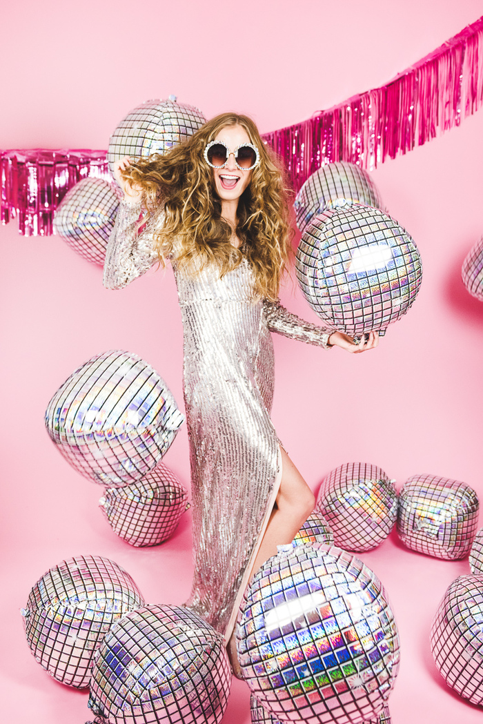 woman with long curly hair in a pink room with a bright pink garland in the back wearing a long silver dress with disco balls all around