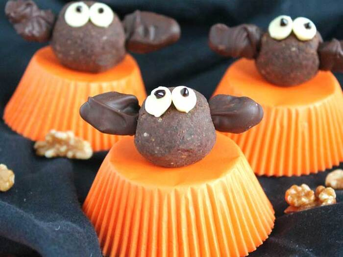 bat energy balls made from chocolate on orange muffin cups with walnuts spread around