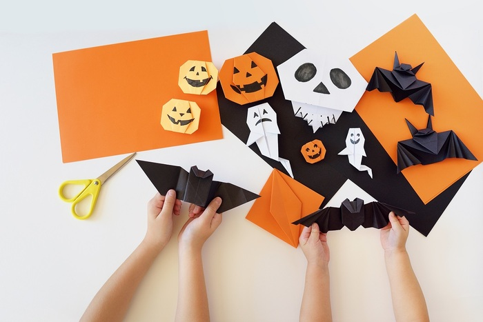 children playing a white table with different colors of paper cutting out bat ghost and pumpkin shapes