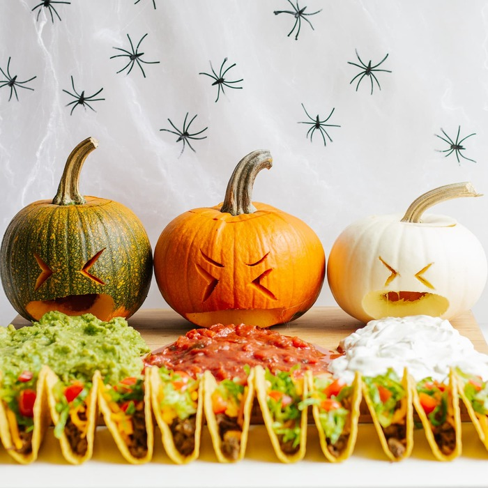 halloween pumpkin tacos with different sauces on a white cloth background with black spiders on