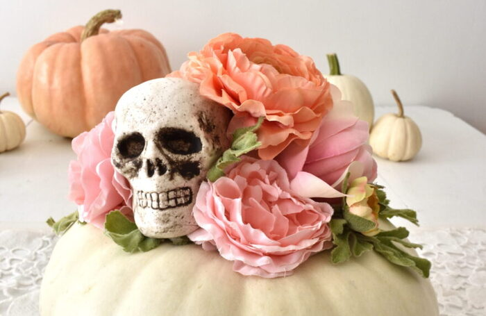 halloween pumpkins on a table in pastel colors white pumpkin with a skull and faux flowers