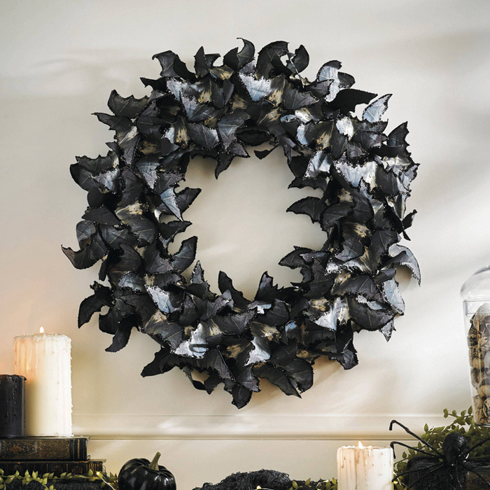 large black halloween wreath made of black paper baths flying in a circle