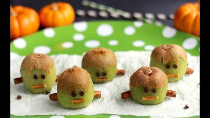 kiwi gohosts monsters halloween snack on a white paper napkin and a green dotted plate with orange pumpkins in the background