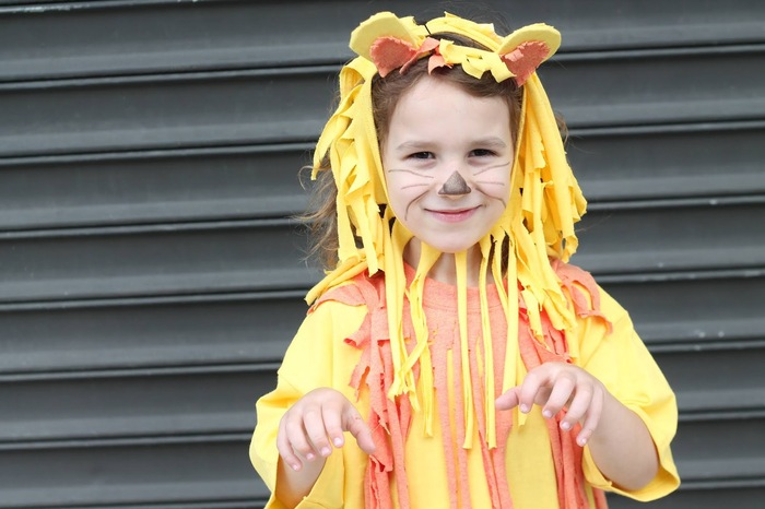little boy in front of a black garage door in a no sew yellow and orange lion costume