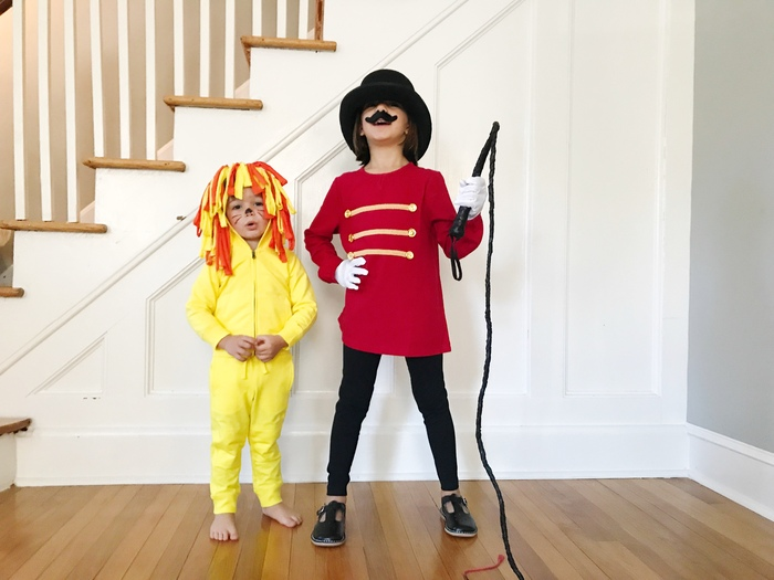 lion halloween two kids next to a staircase dressed as a lion and a circus tamer