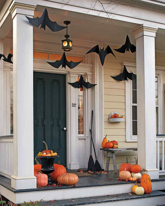 paper bats hanging from the ceiling on a porch with pumpkins and other decorations