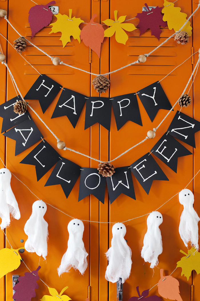 Halloween paper garlands on a bright orange background ghosts leaves and letters