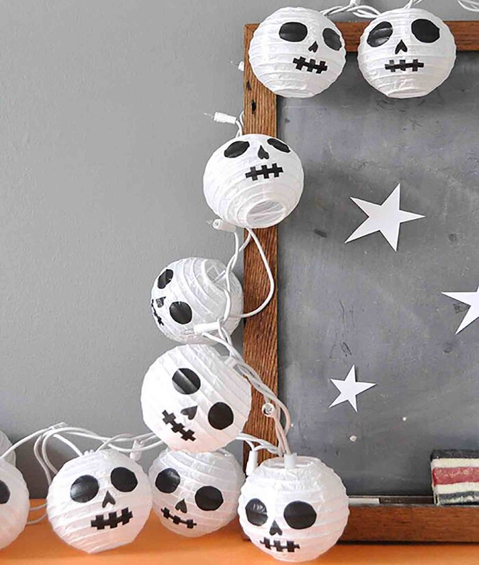 spooky halloween paper lanterns with skull faces on them surrounding a wooden frame