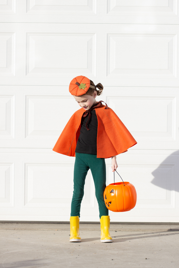 pumpkin cape halloween costume little girl in front of a white wall in a fall inspired costume with a pumpkin lantern