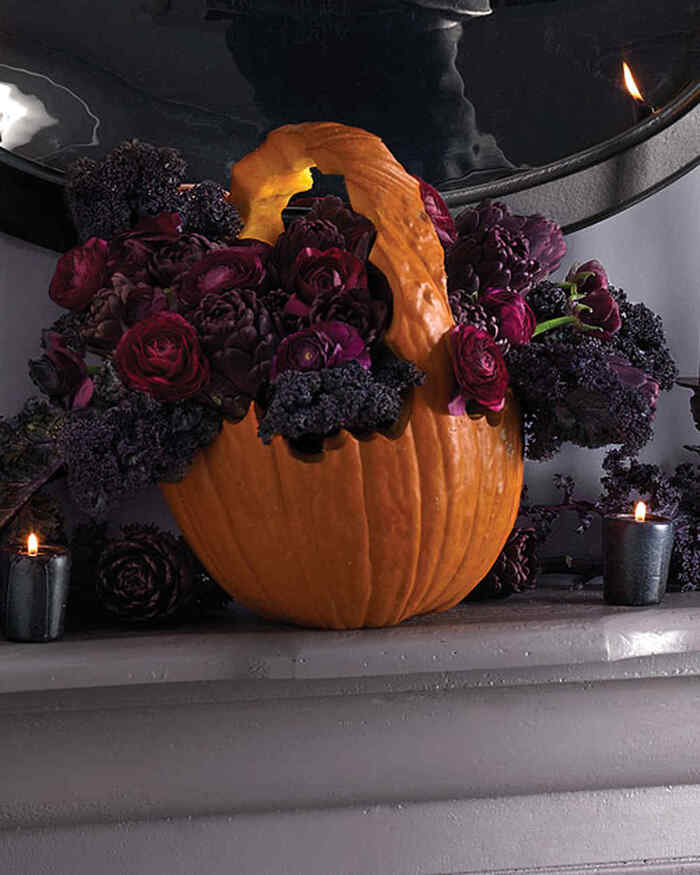 carved pumpkin basket on a mantel with a spooky halloween flower arrangement of dark flowers