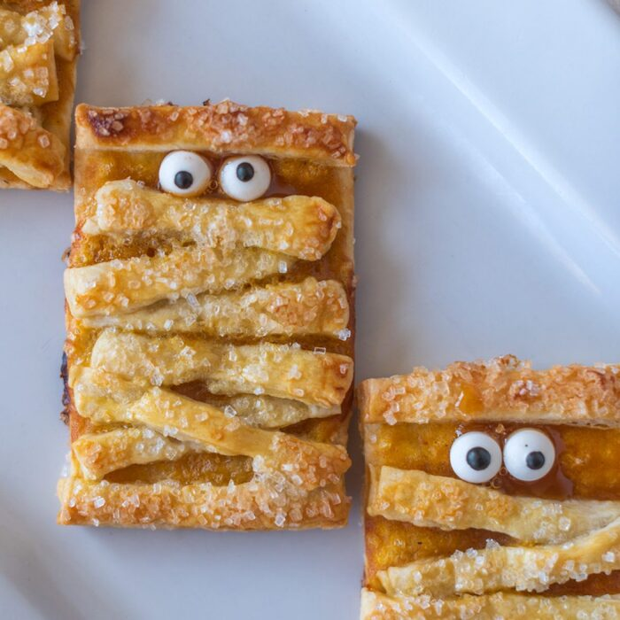 pumpkin mummy cookies close up on a white plate with funny googly eyes