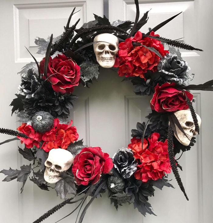 spooky faux flower wreath in red and black with white skulls black feathers and red roses hanging on a white wall