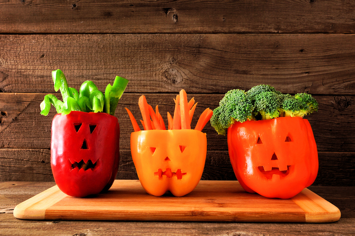 fresh halloween veggies different peppers on a wooden cutting board wooden wall in the background