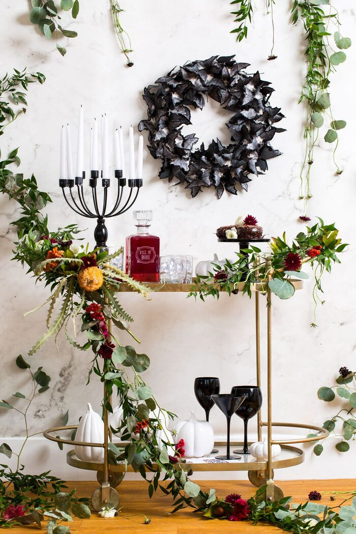 Black halloween wreath on a white wall with living plants and flower arrangements around